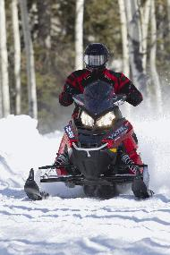 Man rides a red snowmobile over snow.