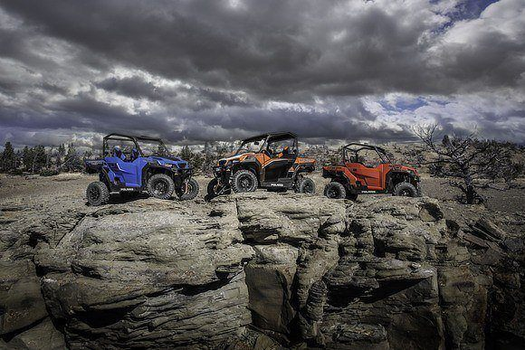 Blue, orange, and red side by  sides on rocky terrain.